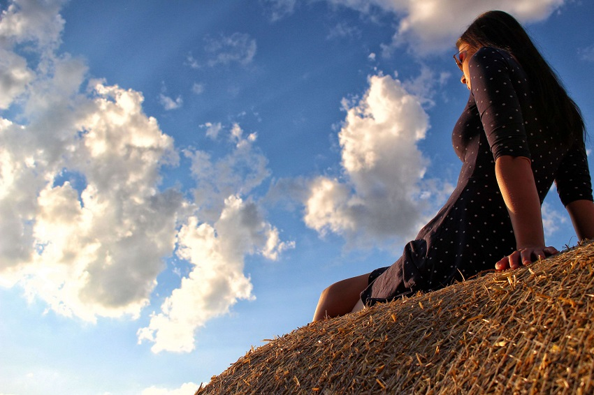 Девушка смотрит на солнце. Фотография